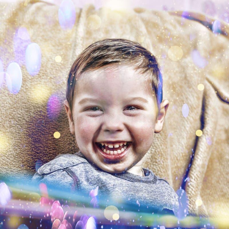 小愉快的男孩笑,当在家坐沙发在圣诞节内部时 免版税库存照片
