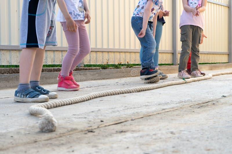 小打比赛-在准备好的绳索的跃迁的儿童男孩和女孩跳跃 对腿的透视 库存照片