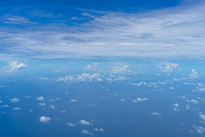 小抽象白色云彩看法与明亮的天空蔚蓝天际和浩大的海海洋背景的从飞行的飞机窗口上 库存照片