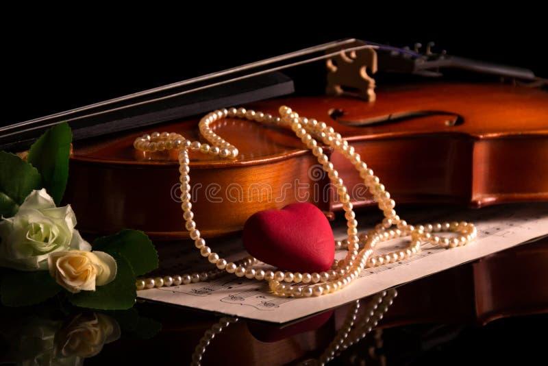 小提琴、音乐笔记和在黑色隔绝的珍珠项链 免版税图库摄影