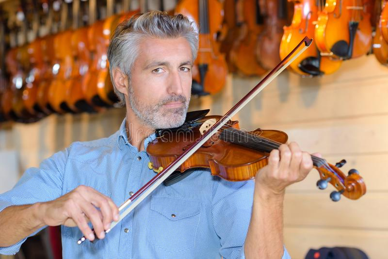 小提琴制造商,当测试小提琴在实验室时 免版税库存图片