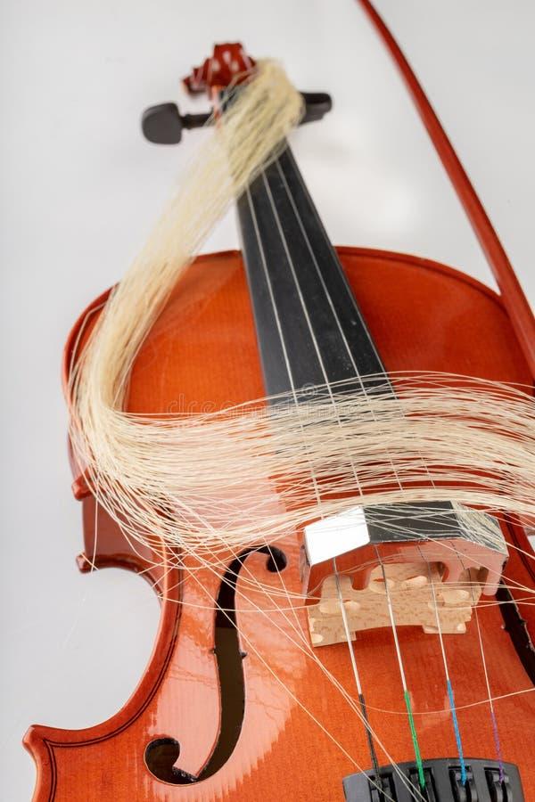 小提琴和弓在轻的背景 一个新的被串起的乐器 图库摄影