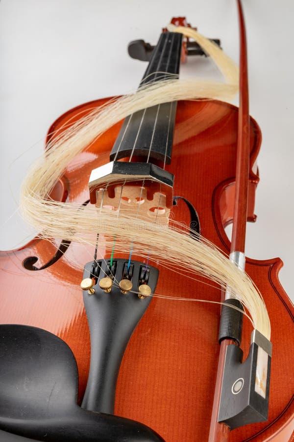 小提琴和弓在轻的背景 一个新的被串起的乐器 免版税库存照片