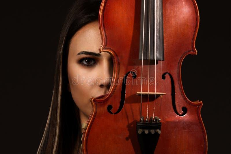 小提琴手与小提琴的妇女画象在背景 免版税库存图片