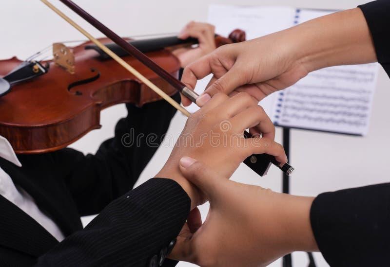 小提琴老师手由接触学生手在串教小提琴学生,为使用弓使用 库存图片