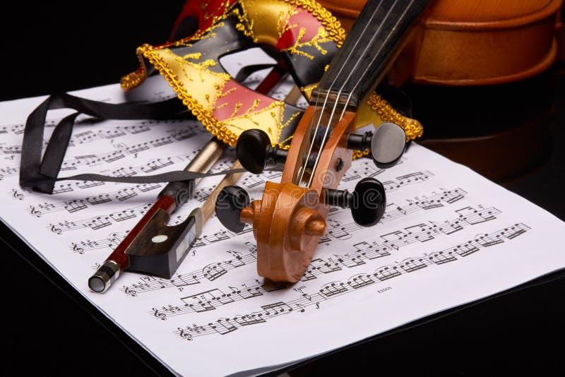 小提琴、剧院面具和笔记 免版税库存照片