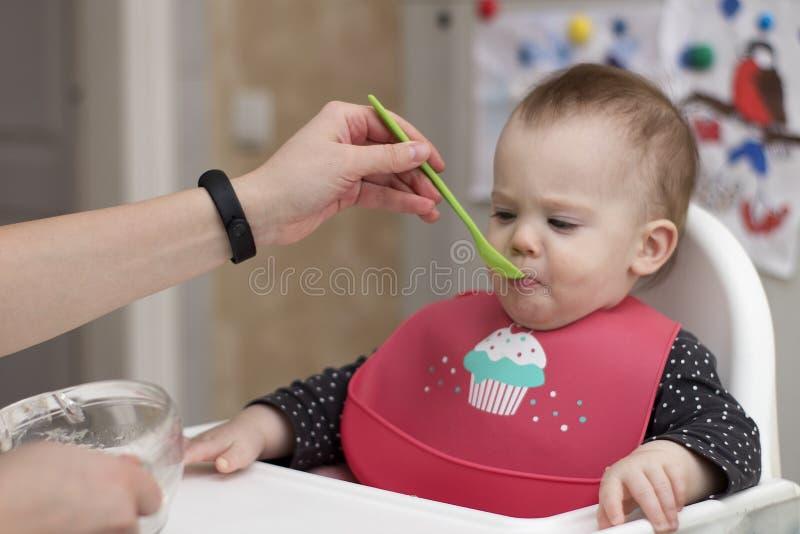 小新出生吃与匙子 免版税库存图片