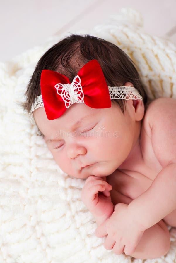 小新出生的女婴画象有一把红色弓的在她的头 孩子休眠 免版税库存照片