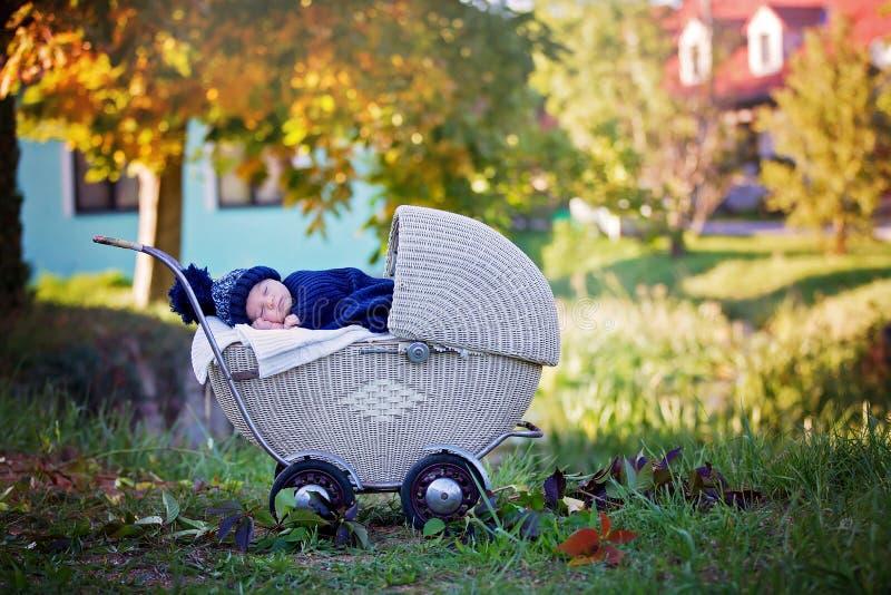 小新出生的男婴,睡觉在老减速火箭的婴儿推车在前面 免版税库存照片