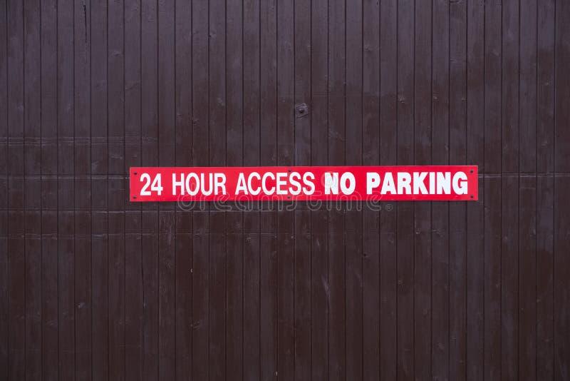 24小时通入禁止停车标志红色和白色在木便门 免版税库存照片