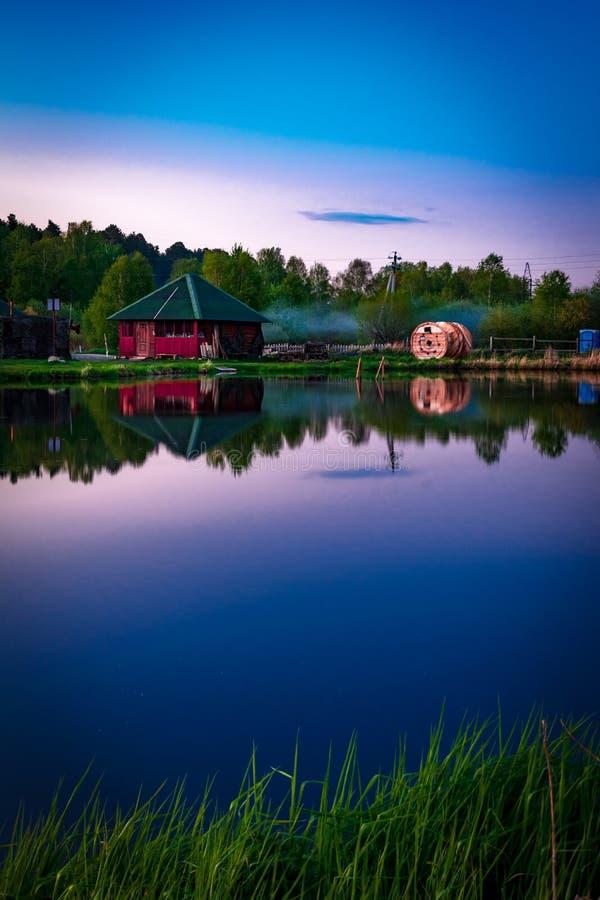 小有烟的村庄红色房子在明显地寂静的水中反射晚上 免版税库存照片