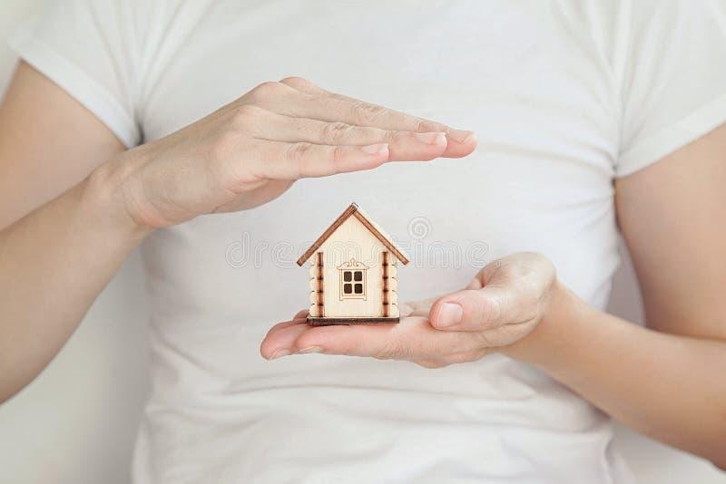 小木房子在妇女` s手上,一只手保护房子的屋顶 库存图片