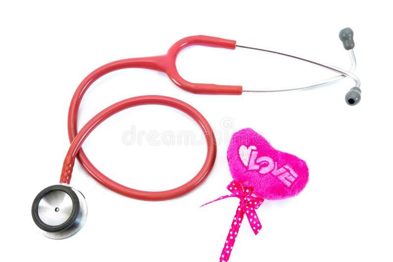 小桃红色心脏枕头和红色听诊器 在心形的桃红色枕头棍子与在白色背景隔绝的听诊器 库存图片