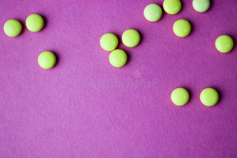 小橙黄美丽的医疗pharmaceptic圆的药片,维生素,药物,在桃红色紫色背景,纹理的抗生素 免版税库存照片