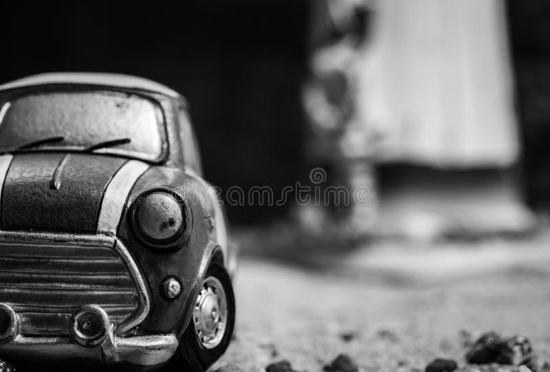 小汽车玩具模型正面图在沙子路的 在被弄脏的背景的黑白微型汽车玩具 动画片缩样汽车 免版税库存照片