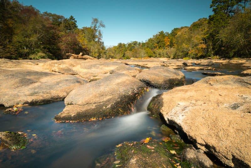 小河和晃动与光滑的河和秋天森林 图库摄影
