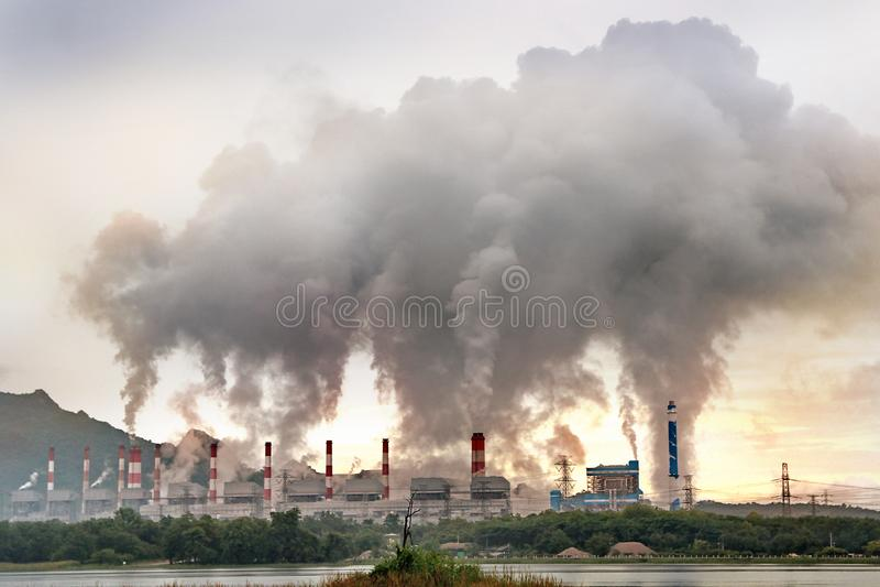 小河和煮沸的被管理的煤炭从许多总合烟囱的火力植物 免版税库存照片