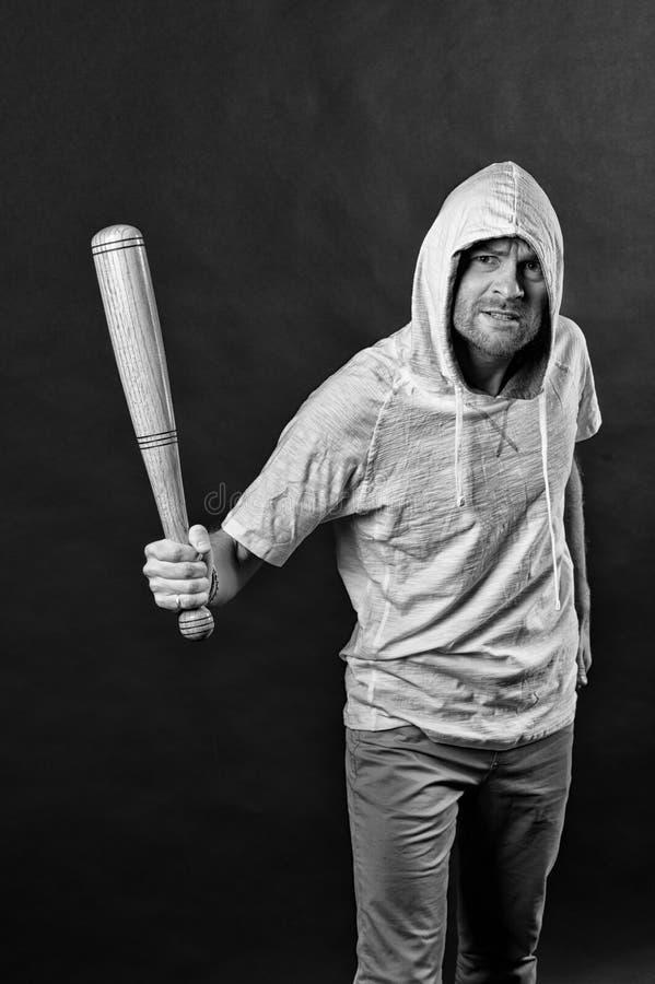 小流氓在有冠乌鸦T恤杉的穿戴敞篷 有胡子的人举行棒球棒 匪徒人威胁与棒武器 侵略或 图库摄影