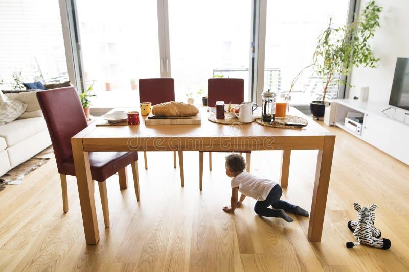 小混杂种族女孩在家在厨房用桌下 免版税图库摄影