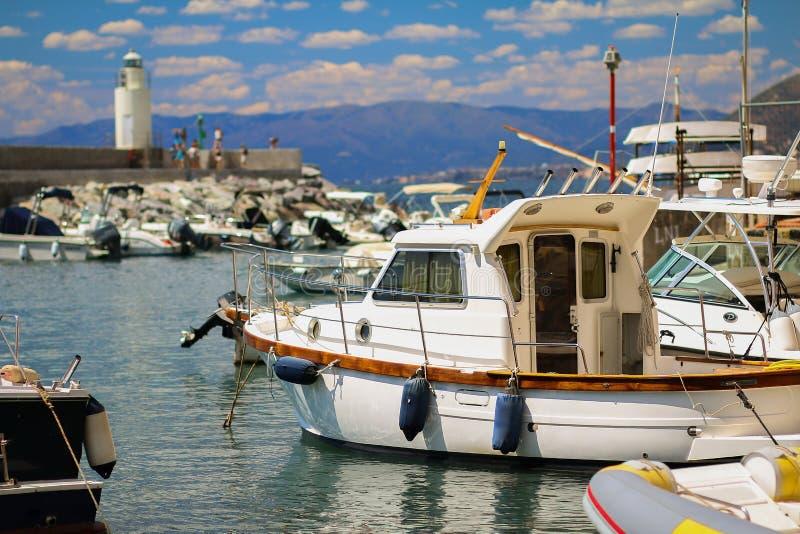 小渔船在卡莫利港口有蓝天和灯塔的 免版税库存照片