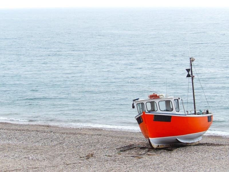 小渔船在有海洋的土地靠岸了在背景中 库存图片