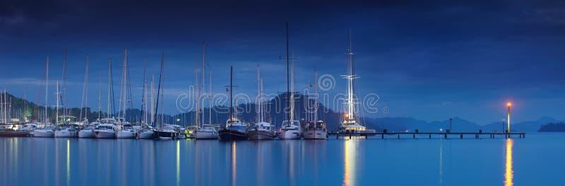 小游艇船坞在与被停泊的游艇的晚上 免版税库存图片