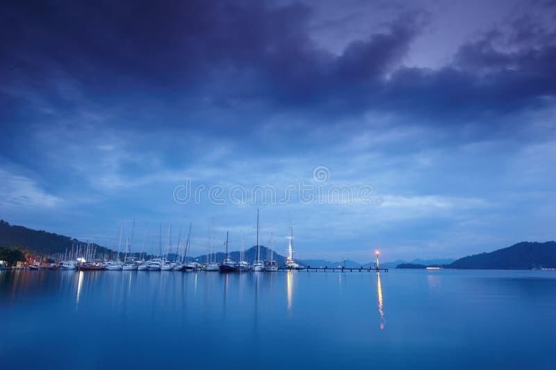 小游艇船坞在与被停泊的游艇的晚上 库存图片