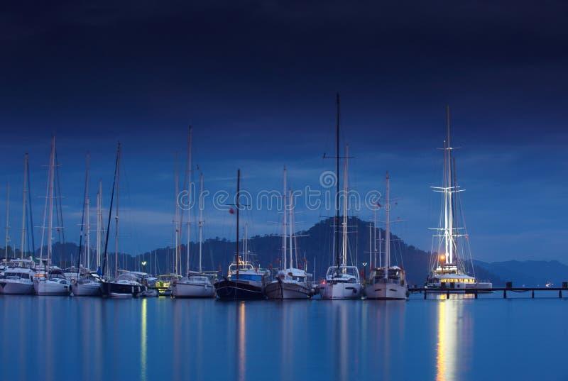 小游艇船坞在与被停泊的游艇的晚上 库存照片