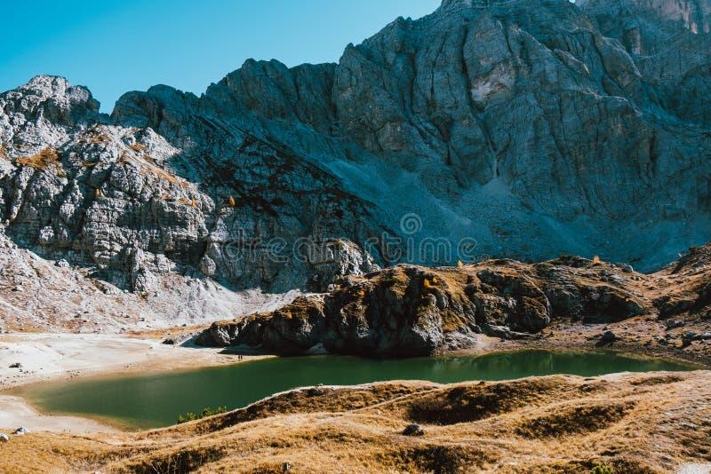 小湖美好的风景看法阿尔卑斯山的与与清楚的天空蔚蓝的太阳光芒上升的behing的落矶山脉在秋天 免版税库存图片