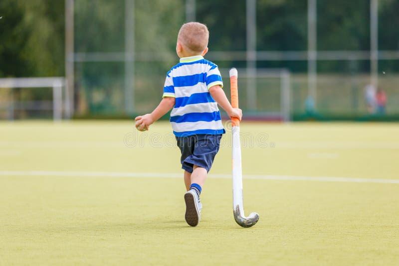 小滑稽的男孩运动场曲棍球用棍子 免版税库存图片