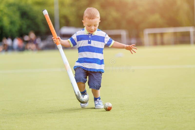 小滑稽的男孩运动场曲棍球 免版税库存图片