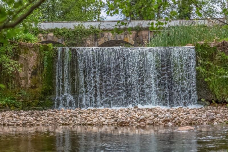 小瀑布看法在河在森林里,有作为背景的老桥梁的 库存照片