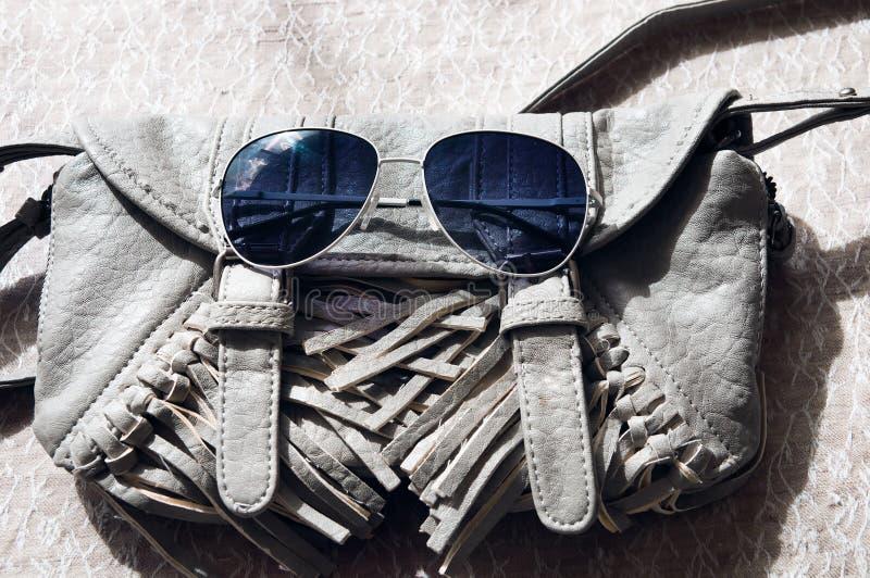 小灰色妇女的提包和太阳镜 免版税库存照片
