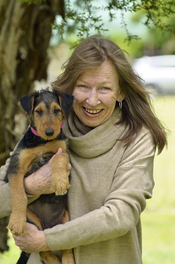 小狗爱抱小狗的微笑快乐的老妇人箱 免版税图库摄影