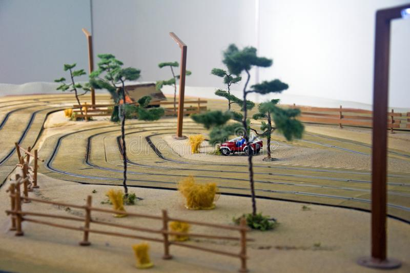 小玩具房子、红色汽车、树和灯笼在玩具轨道 免版税库存图片