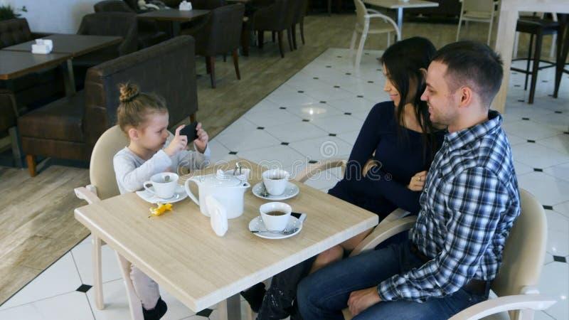 小现代女孩为她咖啡馆的可爱的父母照相 免版税库存照片