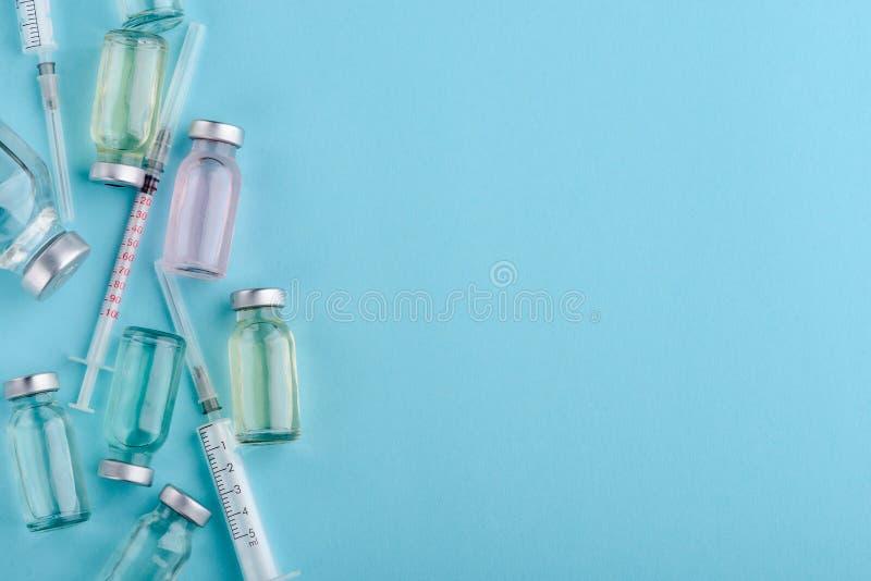 小瓶和注射器在蓝色 免版税库存照片