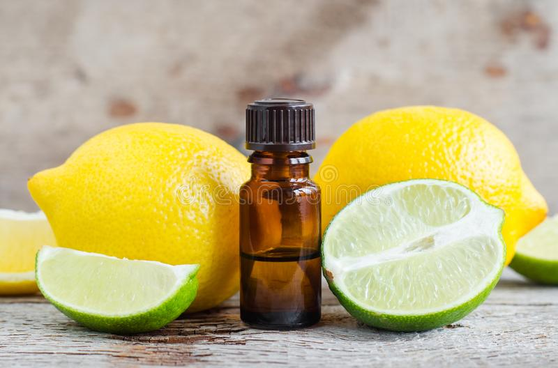 小瓶根本柑橘柠檬和酸橙油在老木背景 芳香疗法,温泉,草药成份 库存照片