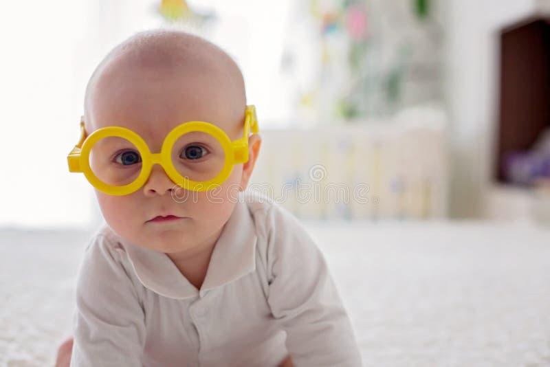 小男婴,小孩,在家使用与滑稽的眼睛玻璃 免版税库存图片