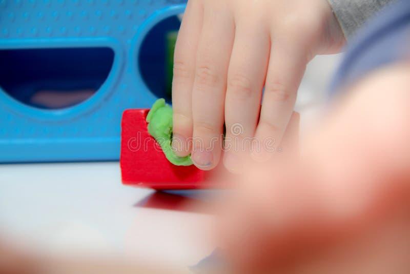 小男孩三岁坐桌和戏剧与彩色塑泥和木和塑料玩具、立方体和模子 免版税库存图片