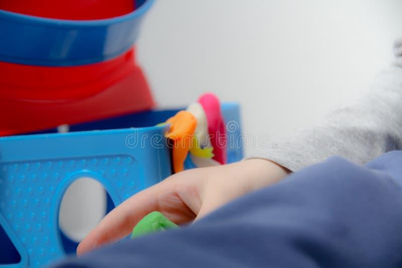 小男孩三岁坐桌和戏剧与彩色塑泥和木和塑料玩具、立方体和模子 库存照片