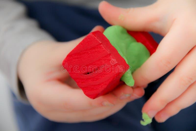 小男孩三岁坐桌和戏剧与彩色塑泥和木和塑料玩具、立方体和模子 库存图片