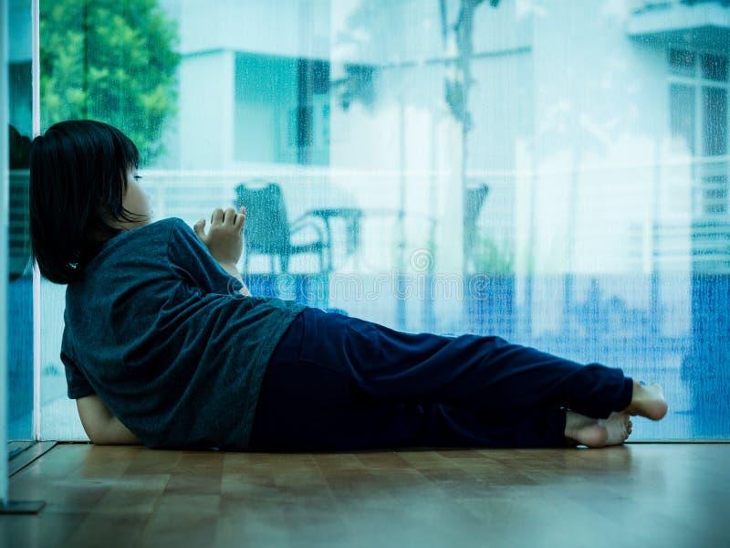 小男孩不快乐哀伤stitting在单独空的屋子和发辫里 哀伤的儿童概念 图库摄影