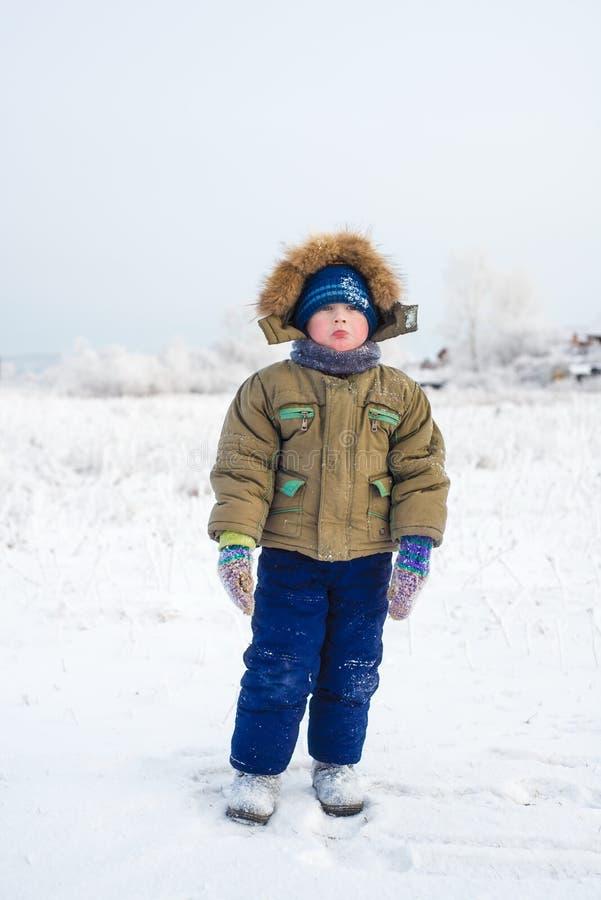 小男孩与一个哀伤的面孔户外冬天 免版税库存照片