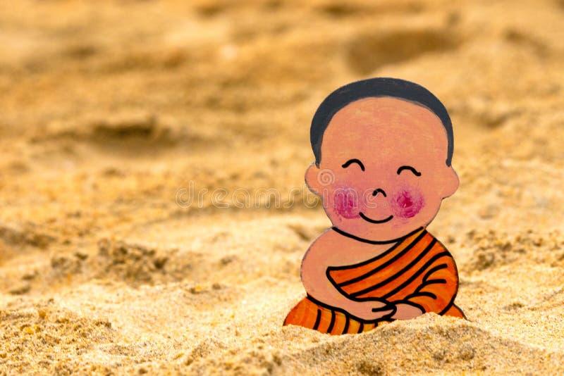 小男孩佛教徒,小菩萨,坐在海滩的沙子 高兴和在莲花坐的微笑 凝思和 免版税库存照片