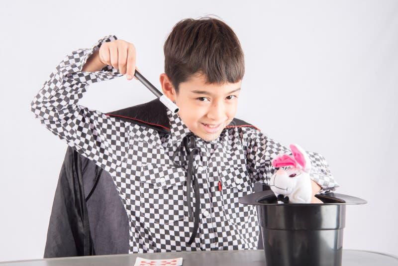 小男孩假装作为与乐趣的魔术师表现 免版税库存照片