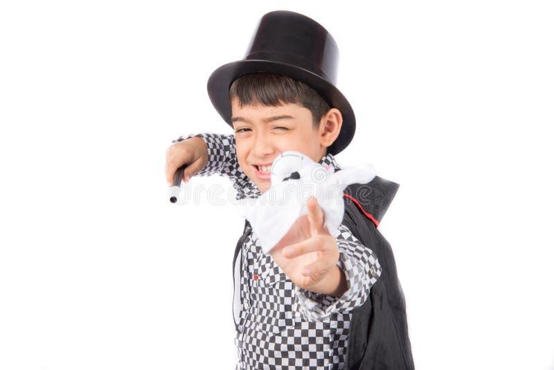 小男孩假装作为与乐趣的魔术师表现 免版税库存图片