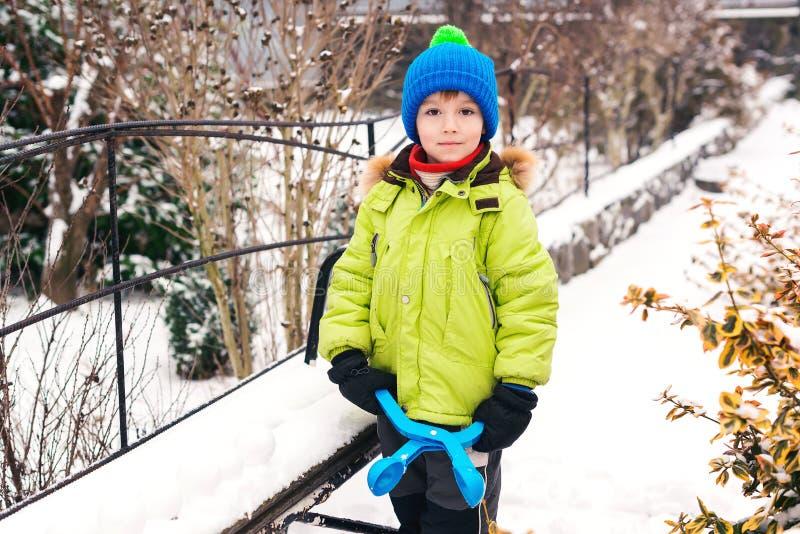 小男孩做与雪球制造商的雪球 儿童愉快的使用的雪 冷的冬天天气 孩子的冬天活动 库存图片