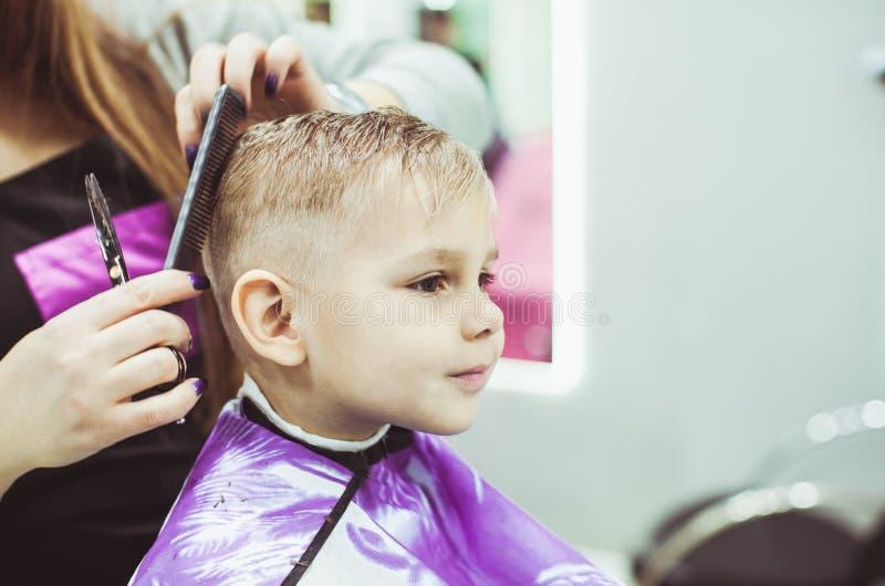 小男孩做发型在美发师 库存图片