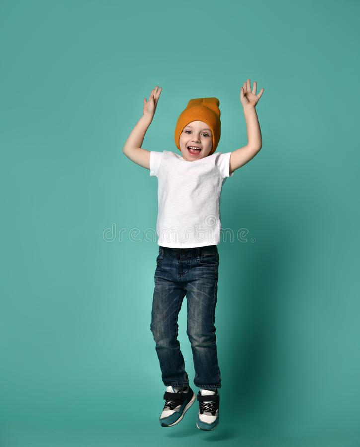 小男孩儿童跳跃的图象被隔绝在绿色背景 免版税库存图片